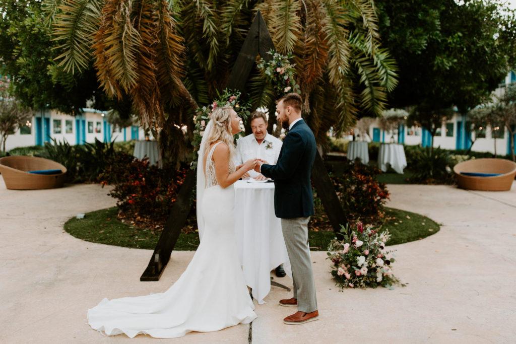 Tropical Garden Bride and Groom Exchanging Wedding Vows During Outdoor Wedding Ceremony   St. Pete Wedding Venue Postcard Inn