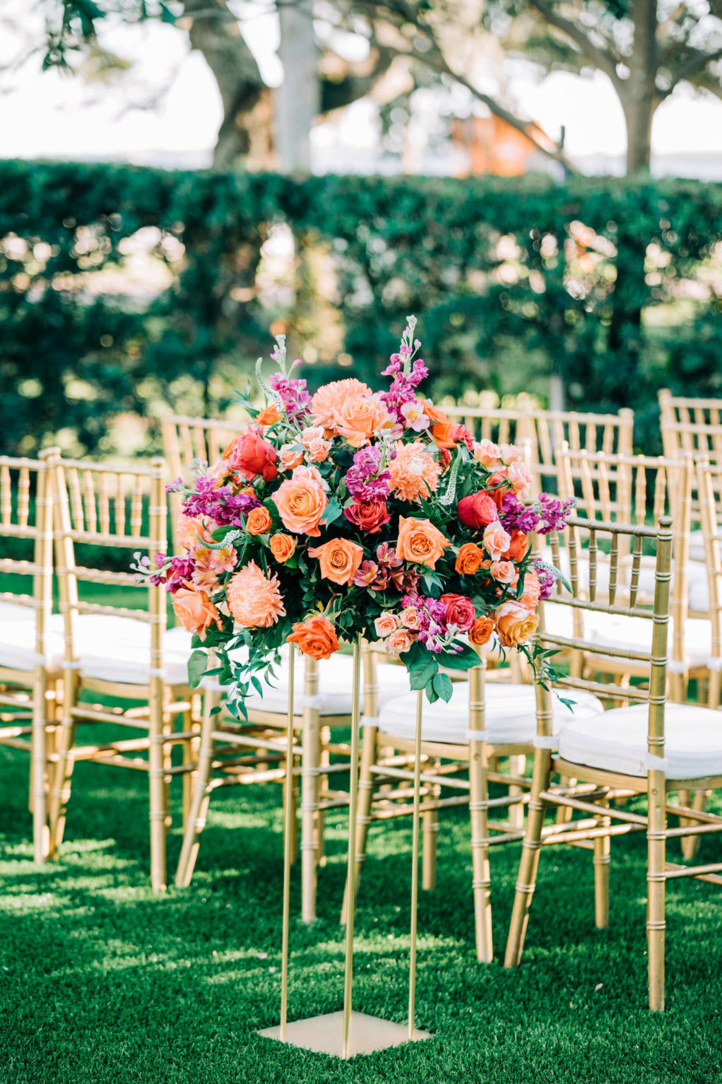 Outdoor Garden Wedding Ceremony Decor, Gold Chiavari Chairs, Gold Stands with Vibrant Colorful Purple, Pink, Orange Roses, Red and Greenery Lush Floral Arrangement   Wedding Venue Tampa Garden Club   Wedding Florist Monarch Events and Design   Wedding Rentals Kate Ryan Event Rentals