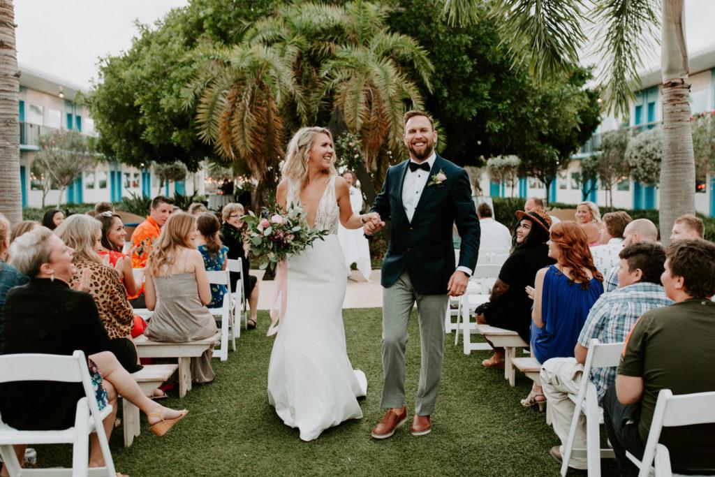 Tropical Garden Bride and Groom Exiting Wedding Ceremony | St. Pete Wedding Venue Postcard Inn