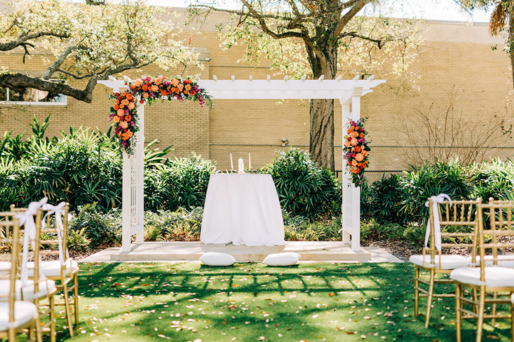 Garden Outdoor Wedding Ceremony Decor, White Pergola with Lush Vibrant and Colorful Floral Arrangements, Greenery, Pink, Orange, Red and Purple Flowers, Gold Chiavari Chairs   Wedding Venue Tampa Garden Club   Wedding Florist Monarch Events and Design   Wedding Rentals Kate Ryan Event Rentals