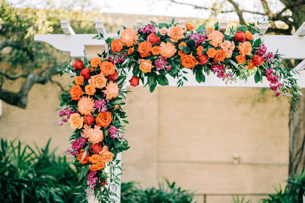 Outdoor Garden Wedding Ceremony Decor, White Pergola with Lush Floral Arrangement, Orange Roses, Pink and Purple Flowers with Greenery   Tampa Bay Wedding Florist Monarch Events and Design
