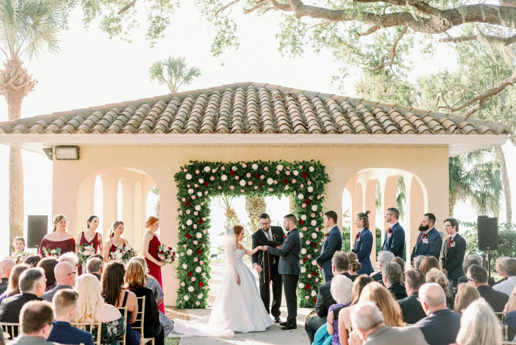 Timeless Romantic Bride and Groom Exchanging Wedding Vows at Gazebo with Greenery Burgundy Red, Blush Pink and White Floral Arch | Tampa Bay Wedding Photographer Dewitt for Love Photography | Sarasota Wedding Venue Powel Crosley Estate