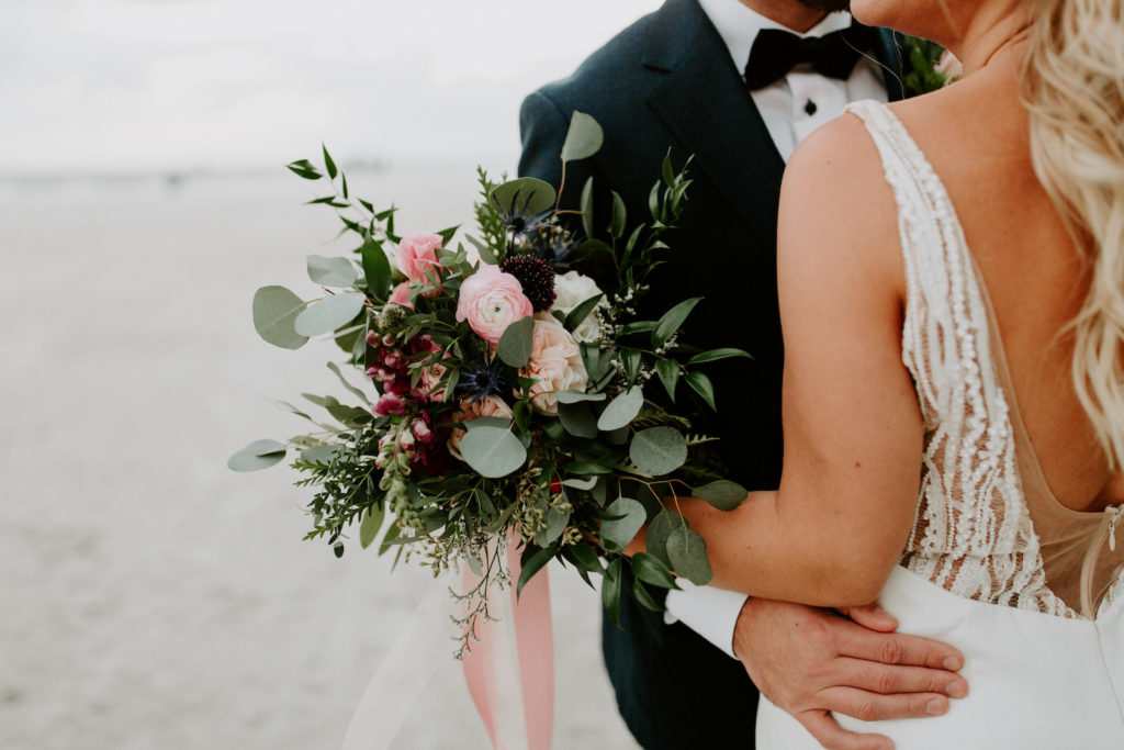 Florida Bride in Fitted Lace and Illusion Plunging V Open Back Wedding Dress and Full Length Veil Holding Wild Greenery Eucalyptus with Pink and Purple Floral Bouquet, Groom in Emerald Green Tuxedo Jacket and Bowtie   St. Pete Wedding Venue Postcard Inn on the Beach