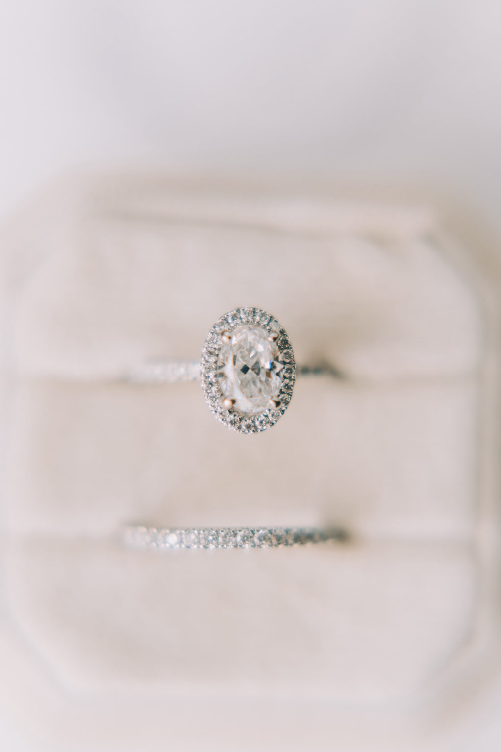 Oval with Halo Diamond Engagement Ring and Thin Diamond Wedding Band in Ivory Velvet Ring Box