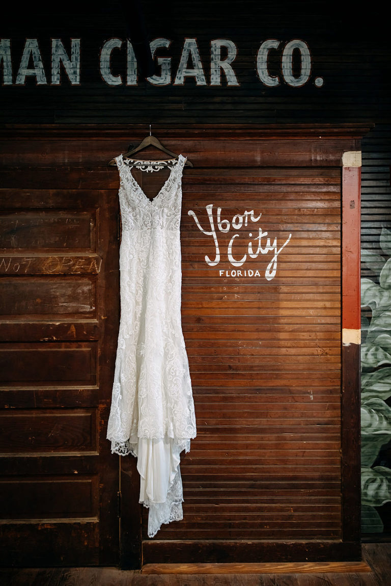 Tampa Bay Vintage Inspired Lace Wedding Dress Hanging In Industrial Wedding Venue   J.C. Newman Cigar Co. in Ybor City Florida