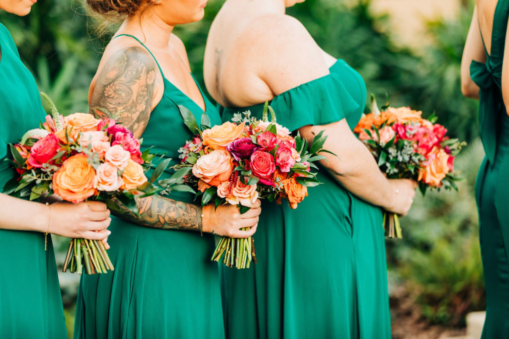 Outdoor Garden Wedding Ceremony, Bridesmaids in Mix and Match Emerald Green Dresses Holding Vibrant Colorful Floral Bouquets, Red, Pink and Orange Roses with Greenery   Tampa Bay Wedding Florist Monarch Events and Design