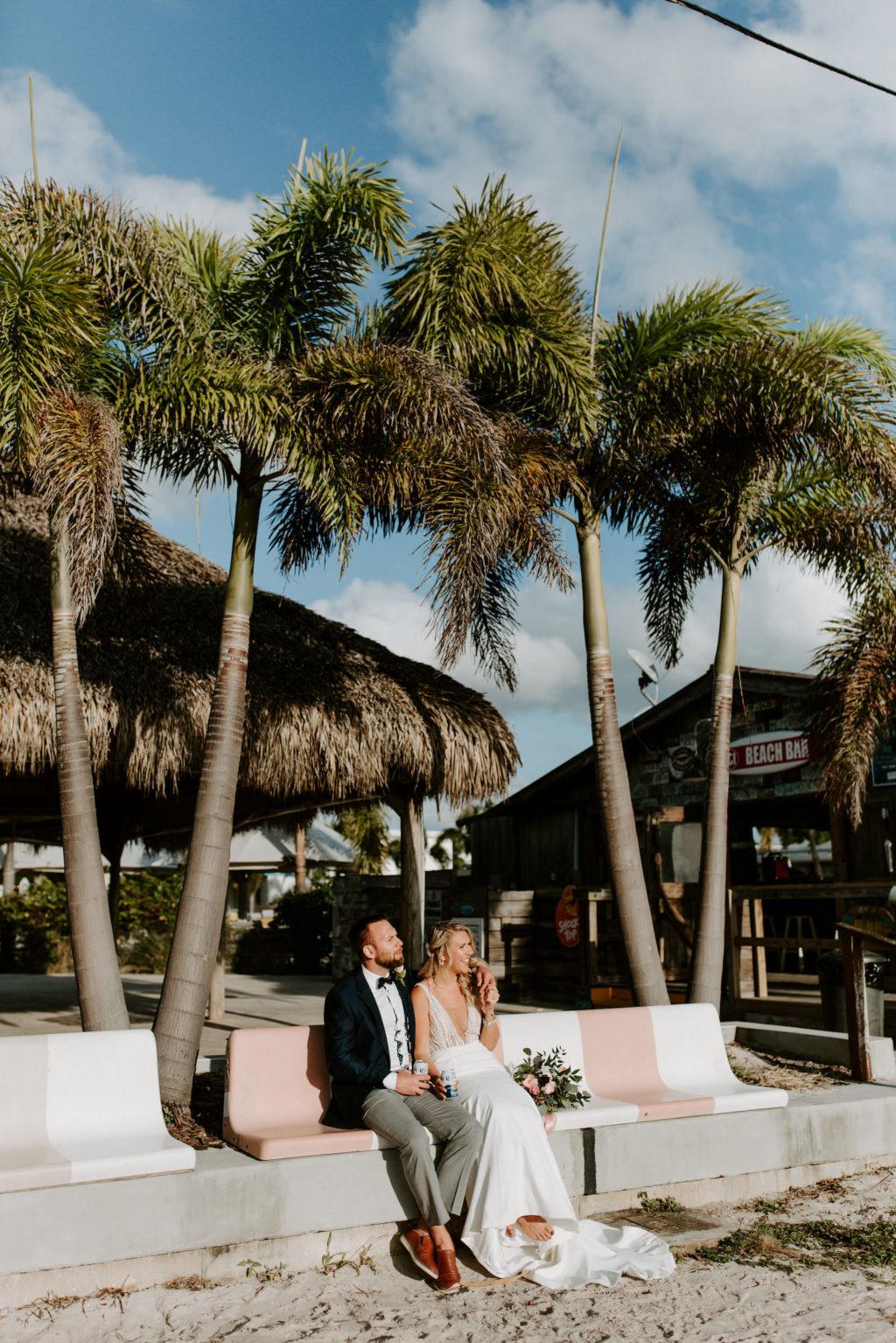 Florida Bride and Groom Sitting on Bench of Sandy Beach   St. Pete Wedding Venue Postcard Inn on the Beach
