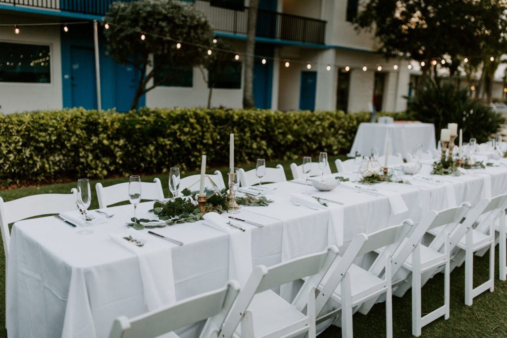 Garden Tropical Wedding Reception Decor, Long Feasting Table with White Linens, Greenery Floral Centerpieces, Candlesticks   St. Pete Wedding Venue Postcard Inn on the Beach