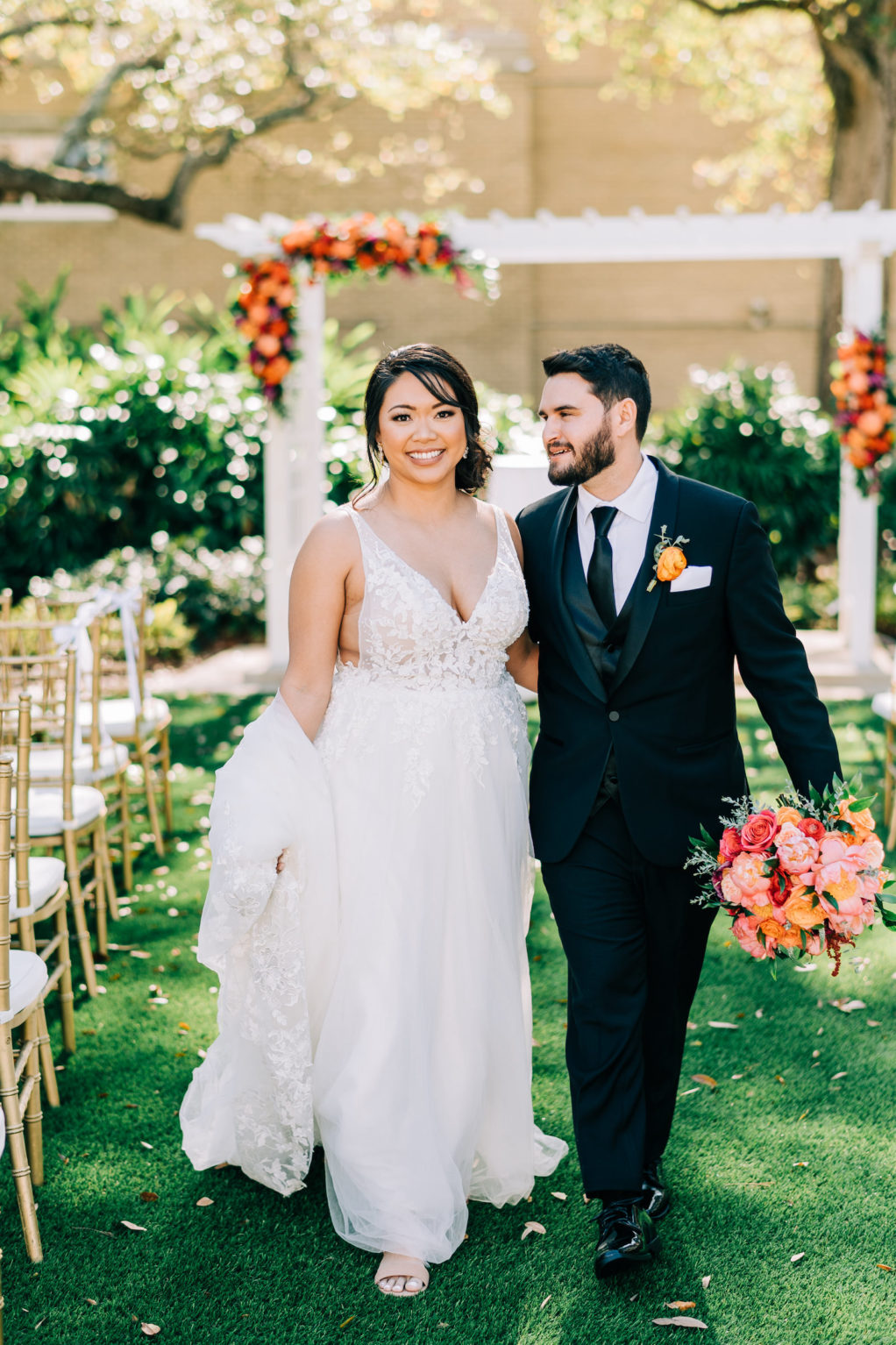 Classic Outdoor Garden Ceremony, Bride and Groom Holding Vibrant Colorful Pink, Orange and Red Bridal Floral Bouquet Walking Together Down the Aisle   Tampa Bay Wedding Florist Monarch Events and Design   Wedding Venue Tampa Garden Club