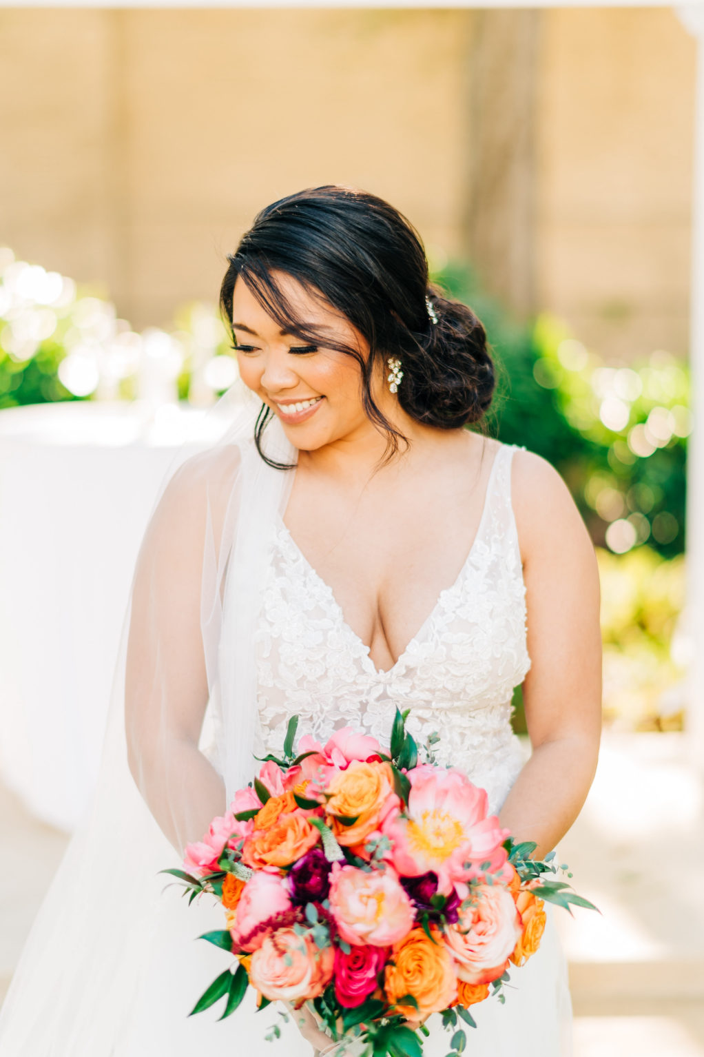 Classic Bride in Plunging V Neckline Lace Wedding Dress Holding Vibrant Colorful Pink, Orange Roses and Greenery Floral Bouquet   Tampa Bay Wedding Florist Monarch Events and Design