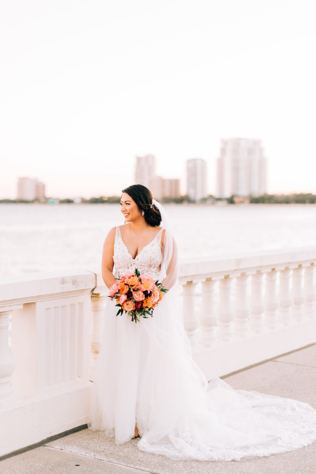 Tampa Bay Bride in Classic Lace Plunging V Neckline Tule A-Line Wedding Dress Holding Vibrant Colorful Orange and Pink Floral Bouquet