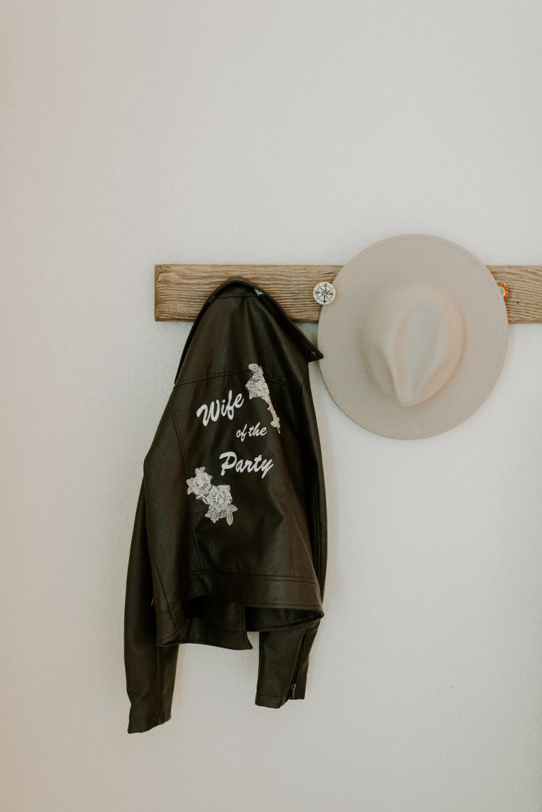 """Black Leather Personalized Embroidered """"Wife of the Party"""" Bride Jacket Hanging Next to Neutral Cowboy Hat Wedding Accessories"""