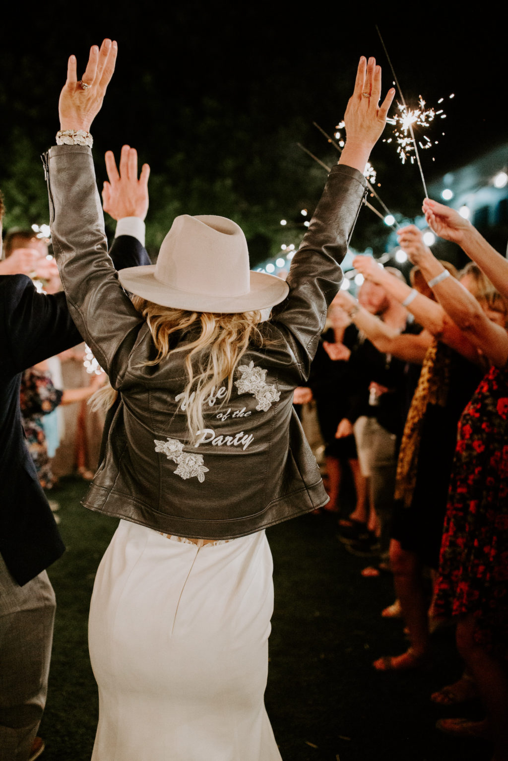 """Fun Bride Wearing Black Leather Embroidered """"Wife of the Party"""" Jacket Over Wedding Dress and Cowboy Monroe Rancher Hat"""