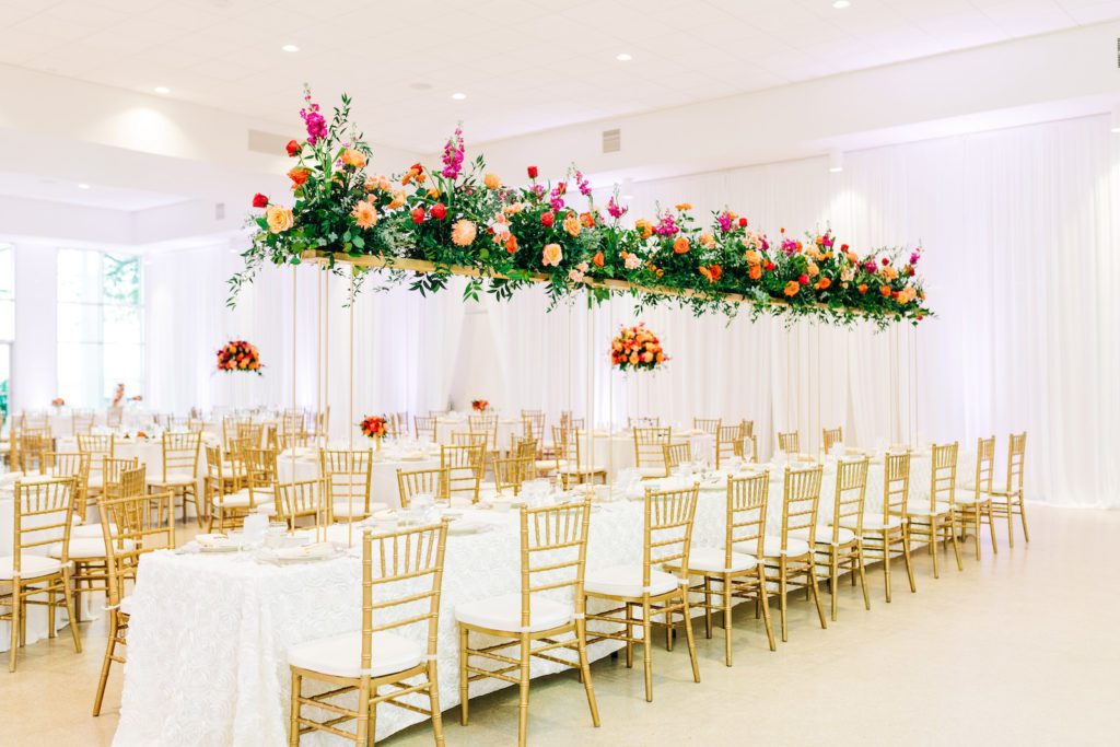 Romantic Garden Wedding Reception Decor, Long Feasting Tables with White Floral Table Linens, Gold Chiavari Chairs, Tall Long Rectangular Gold Stand with Lush Vibrant Colorful Floral Arrangements, Greneery, Pink, Orange and Red Flowers, Linen Drapery   Tampa Bay Wedding Florist Monarch Events and Design   Wedding Rentals Kate Ryan Event Rentals   Wedding Venue Tampa Garden Club