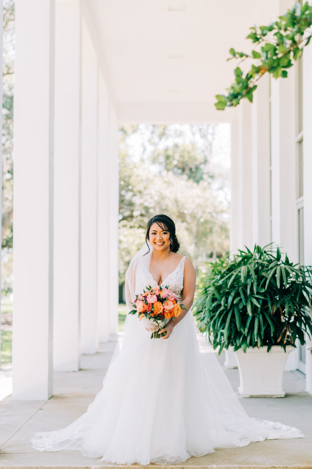 Classic Bride in Plunging V Neckline Lace Strap and Tulle A-Line Skirt Wedding Dress Holding Vibrant Colorful Pink and Orange Floral Bouquet   Tampa Bay Wedding Florist Monarch Events and Design   Wedding Venue Tampa Garden Club
