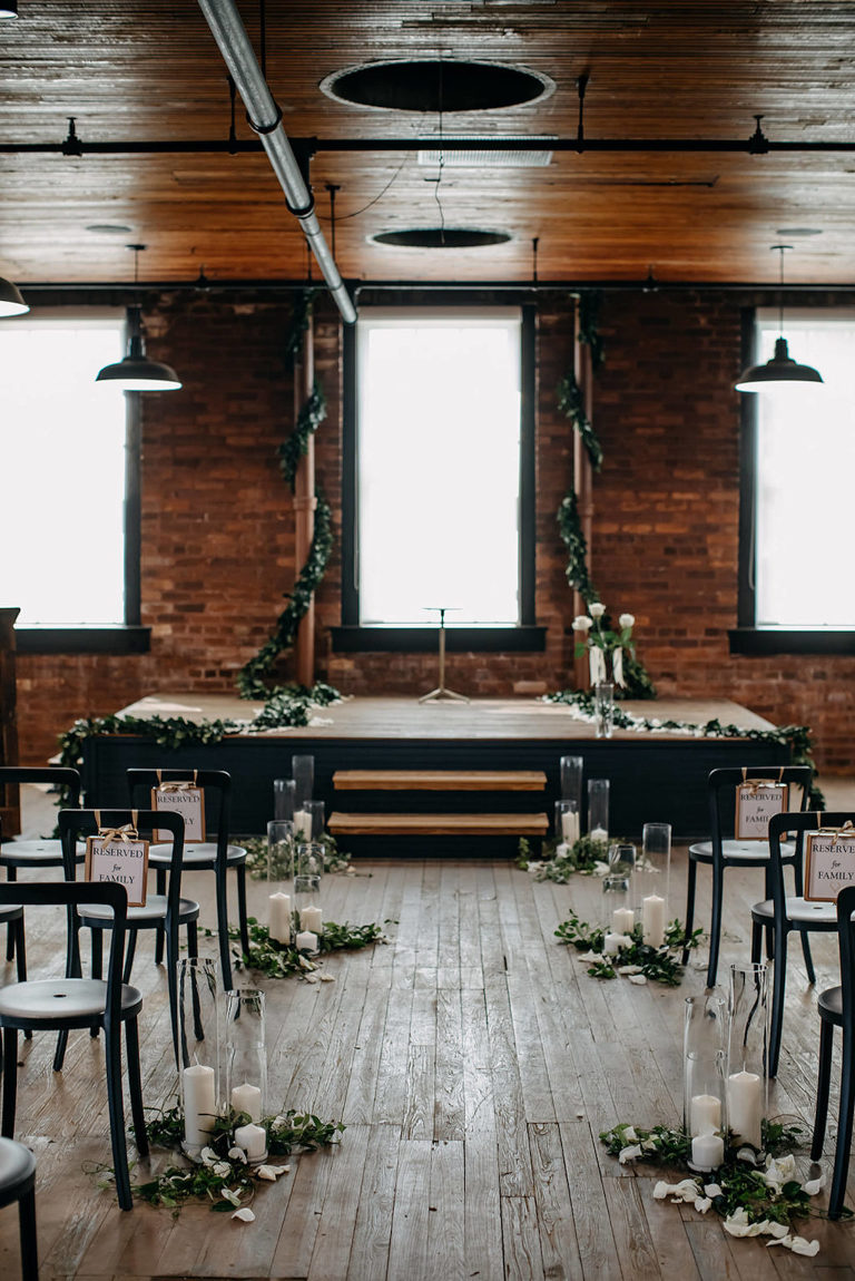 Vintage Inspired Tampa Bay Wedding Ceremony Decor, Simplisitic Brick Exposed Industrial venue, Metal Black Chairs, decorated with Candles, White Rose Petals, and Greenery, Ivy and Vines Wrapped Around Staircase   Unique Florida Wedding Venue J.C. Newman Cigar Co. in Ybor City