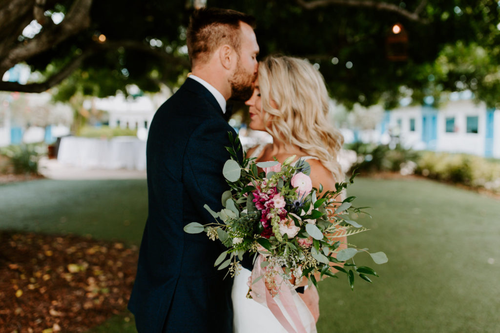 Tampa Bay Bride Holding Wild Floral Bouquet with Greenery Eucalyptus, Pink and Purple Flowers, Groom Kissing Bride's Forehead