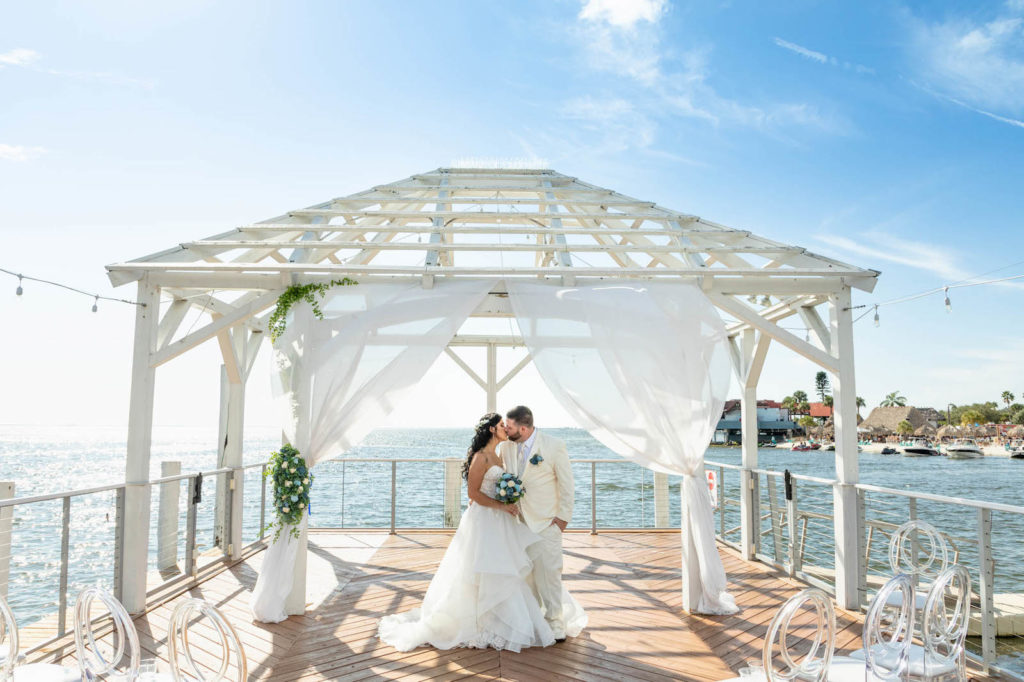 Waterfront Wedding Ceremony with Overwater Pier and White Pergola with Draping and Greenery | Tampa Wedding Venue The Godfrey
