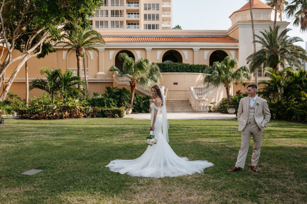 Bride Wearing Off the Shoulder Badgley Mischka Wedding Dress, Groom Wearing Tan Suit Outside Wedding Venue Ritz Carlton Sarasota | Tampa Bay Wedding Dress Shop Truly Forever Bridal