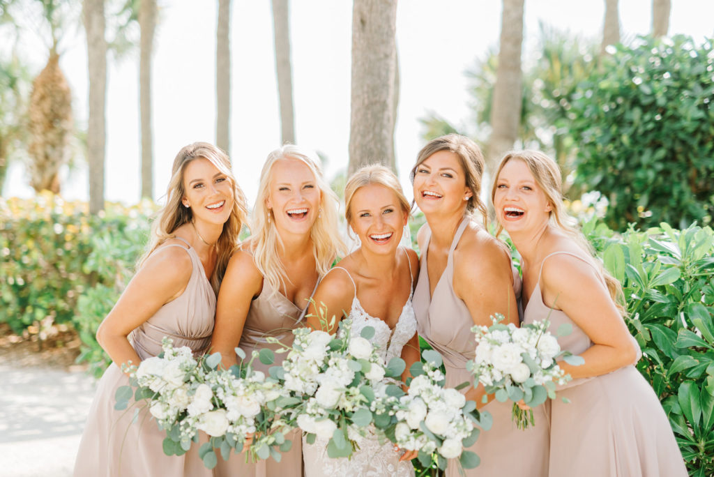 Natural Classic Bride in Romantic Spaghetti Strap Lace Wedding Dress and Bridesmaids in Dusty Rose, Mauve Dresses Holding White Roses and Eucalyptus Greenery Floral Bouquets