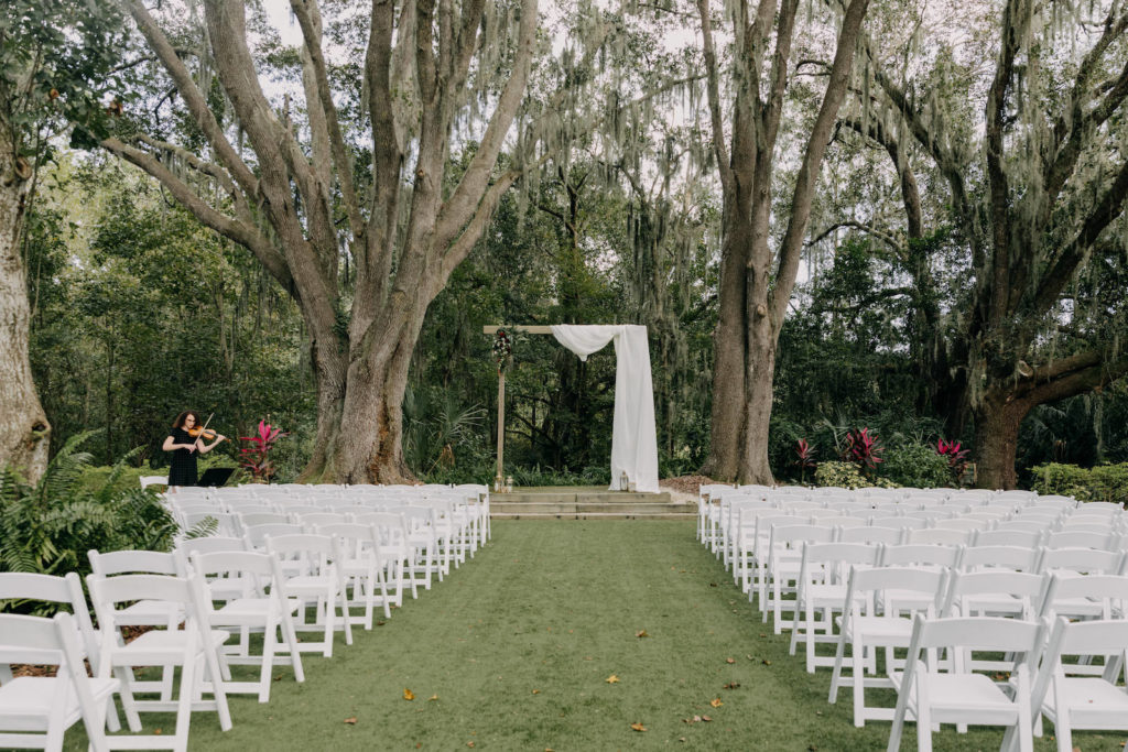 Outdoor Garden Wedding Ceremony, Wooden Rectangular Arch with White Drapery, White Folding Chairs | Tampa Bay Wedding Photographer Amber McWhorter Photography | Wedding Venue The Secret Garden at Paradise Spring