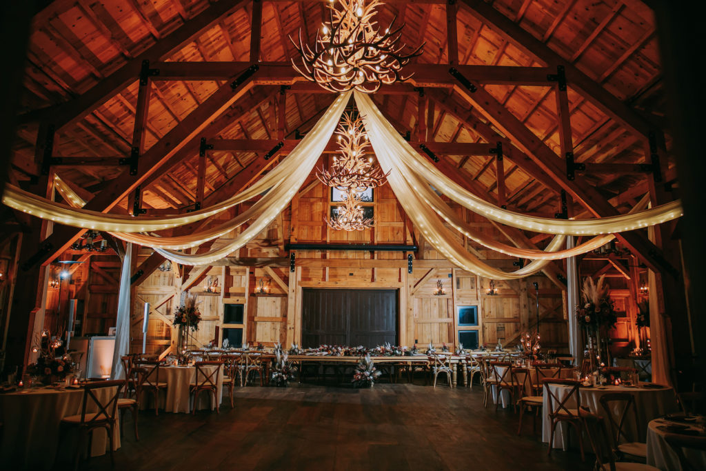 Rustic Florida Barn Wedding Reception, Draped Linens on Ceiling with String Lights, Deer Antler Chandeliers, Long Feasting Table for Wedding Party and Round Tables for Guests | Tampa Wedding Venue Mision Lago Estate | Mision Lago Ranch