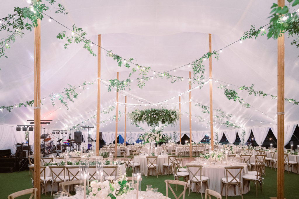 Luxurious Elegant Classic Florida Outdoor Tent Wedding Reception Decor, White Linen Draping, String Lights with Greenery Vines and a Lush Greenery Leaves Wreath Chandelier, Round and Long Tables with Taupe Tablecloths, Wooden Cross Back Chairs, Candlesticks in Glass Hurricane Tumblers