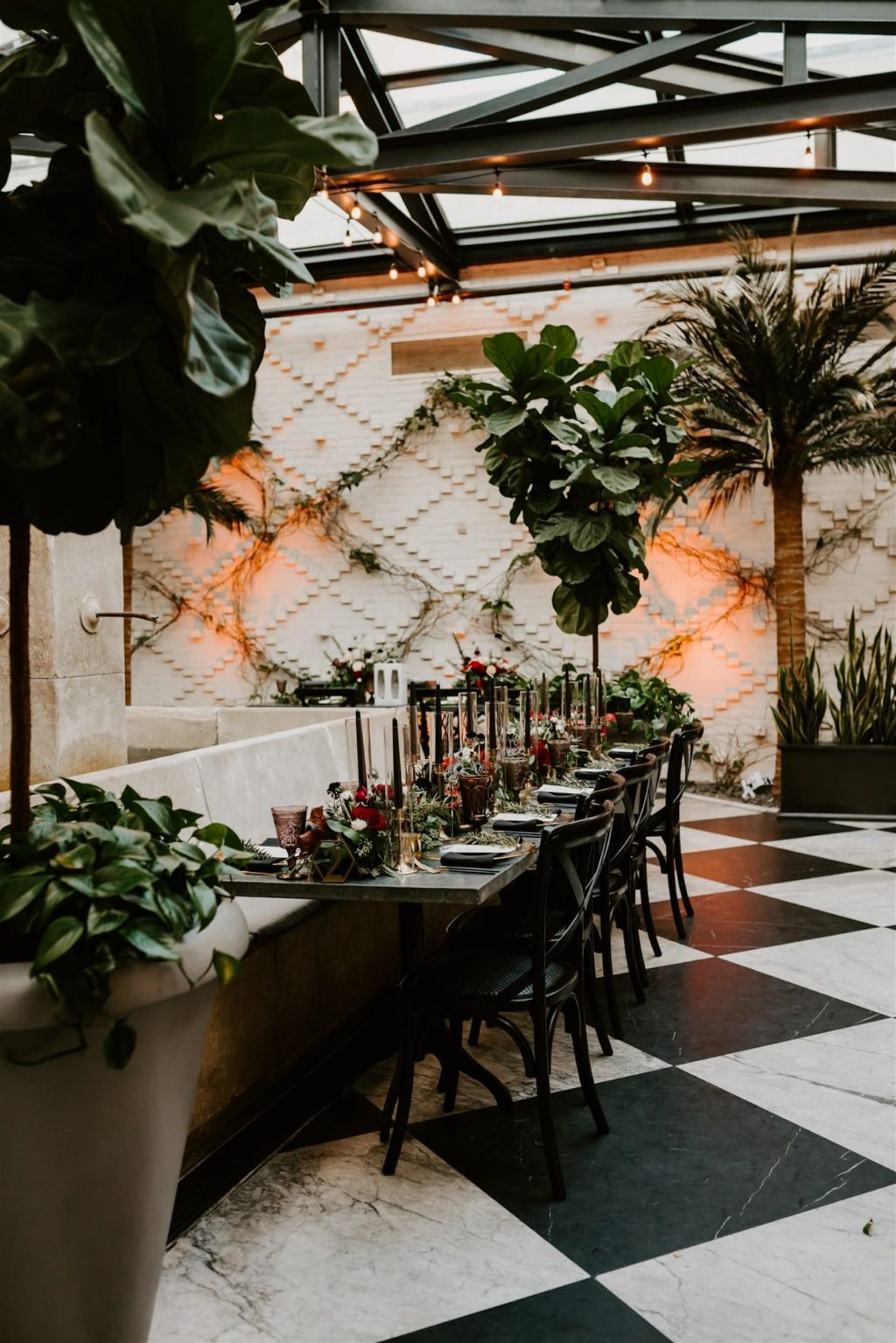 Downtown Tampa Industrial Intimate Historic Wedding with Atrium Conservatory Dinner Reception under Canopy of String Lights | Long Feasting Banquet Tables with Black and Gold Candlesticks and Black Cross Back Chairs | Winsor Event Studio