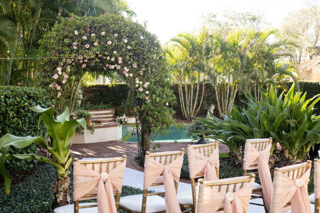 Small Intimate South Tampa Backyard Wedding Ceremony with Greenery Ceremony Arch and Gold Chiavari Chairs with Pink Bow Sashes | Tampa Bay Rental Company Outside the Box Event Rentals