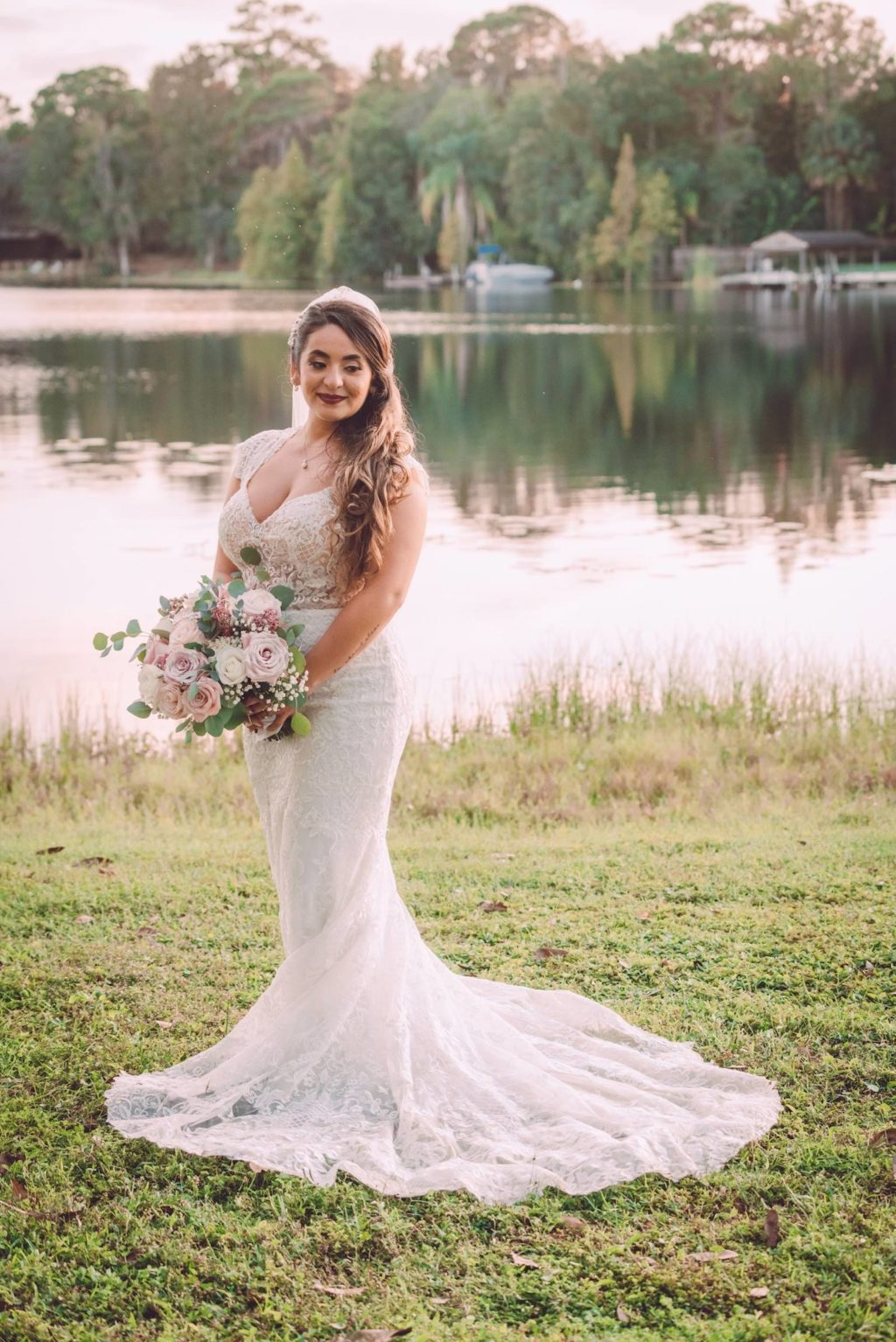 Romantic Bride Standing in Front of Lake Wearing Lace Cap Sleeve V Neckline Nude Bodice and White Skirt Wedding Dress Holding Blush Pink, Ivory and Mauve Roses with Eucalyptus Greenery Leaves Floral Bouquet   Tampa Bay Wedding Photographer Bonnie Newman Creative   Wedding Dress Shop Truly Forever Bridal