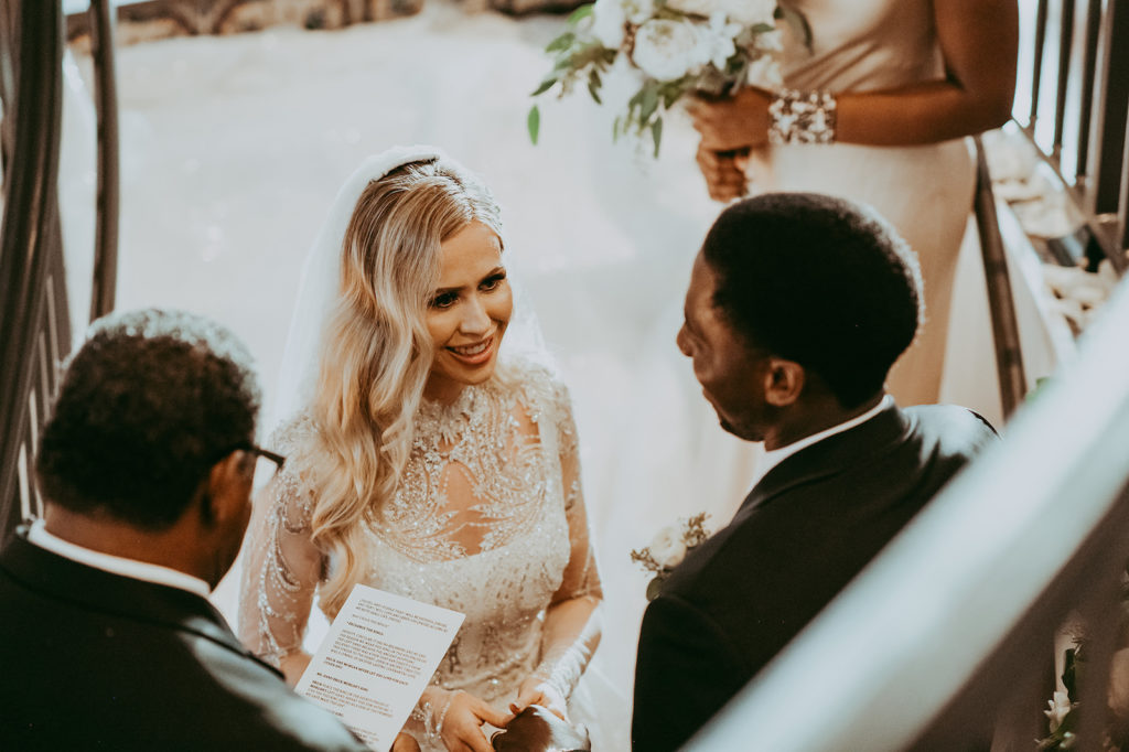 Elegant Timeless Bride Wearing Long Sleeve Rhinestone Crystal Embellished Illusion High Neck Wedding Dress Bodice Exchanging Wedding Vows with Groom
