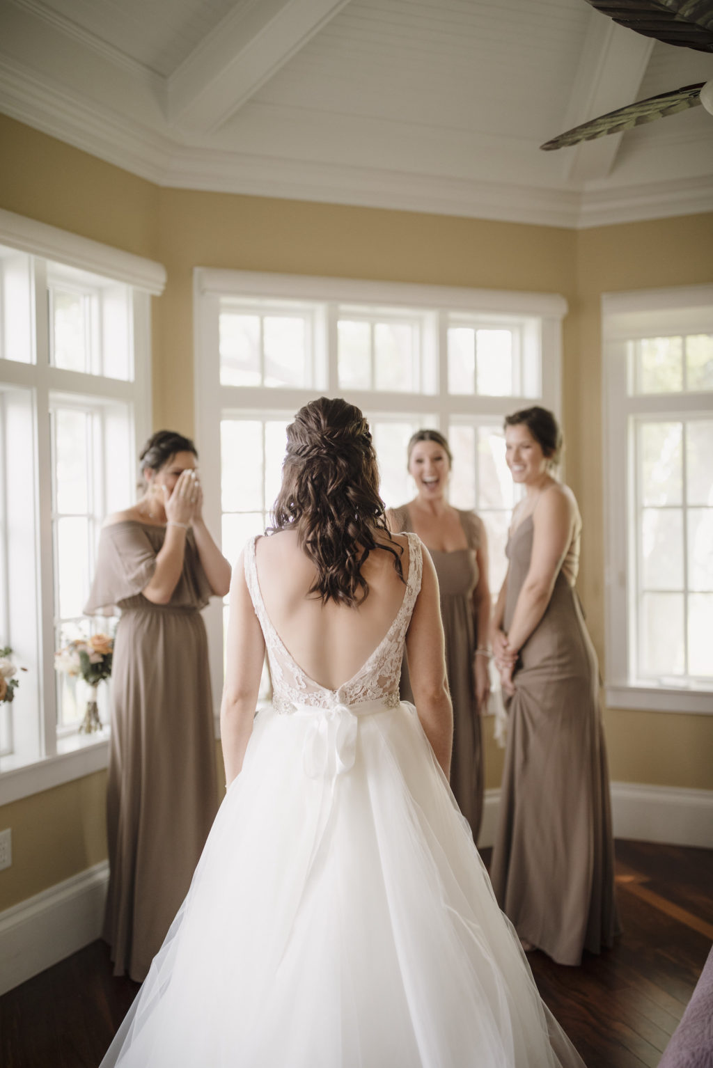 Bride in Low Back Lace Detail Ballgown Wedding Dress   Florida Bride in her Dress First Look with Bridesmaids   Bridesmaids in Mix and Match Taupe Bridesmaid Dresses Portrait   Paloma Blanca, Overskirt: Hayley Paige Ballgown   Bridesmaids in Show Me Your MuMu