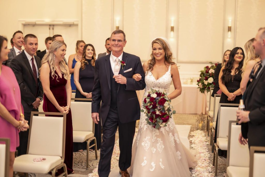 Florida Bride Walking with Dad Down the Wedding Ceremony Aisle Holding Burgundy Roses Floral Bouquet