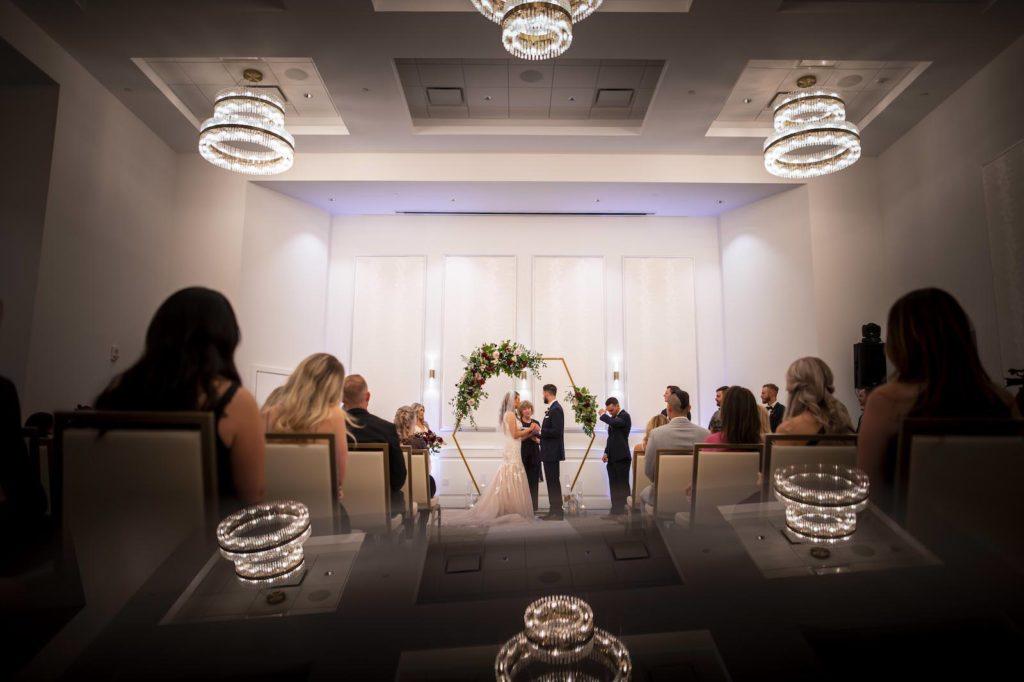 Florida Bride and Groom Exchanging Wedding Vows During Ballroom Ceremony, Gold Geometric Hexagonal Arch with Floral Arrangements | Tampa Bay Wedding Planner Coastal Coordinating | Wedding Venue The Karol Hotel