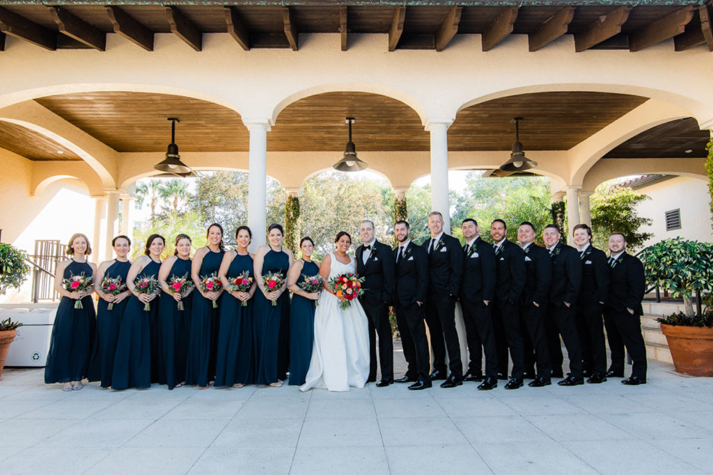 Bride Holding Colorful Jewel Toned Floral Bouquet, Groom in Black Tuxedo, Bridesmaids in Matching Navy Blue Halter Dresses, Groomsmen in Black Suits