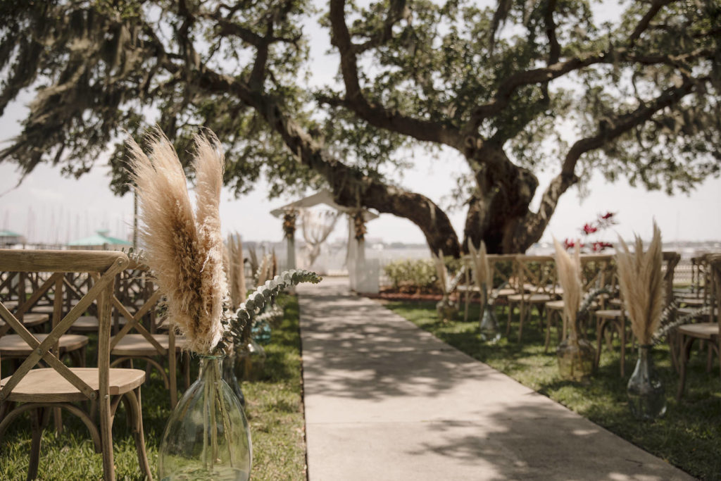 Waterfront Wedding Ceremony with Pampas Leaves and Greenery Adorning the Aisle   Sarasota Wedding Planner Kelly Kennedy Wedding and Events