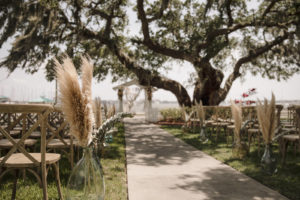 Waterfront Wedding Ceremony with Pampas Leaves and Greenery Adorning the Aisle | Sarasota Wedding Planner Kelly Kennedy Wedding and Events