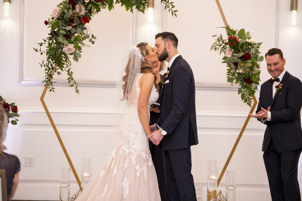 Florida Bride and Groom Exchanging Wedding Ceremony First Kiss Under Gold Geometric Hexagonal Arch with Greenery and Blush Pink, Burgundy Roses   Tampa Bay Wedding Planner Coastal Coordinating
