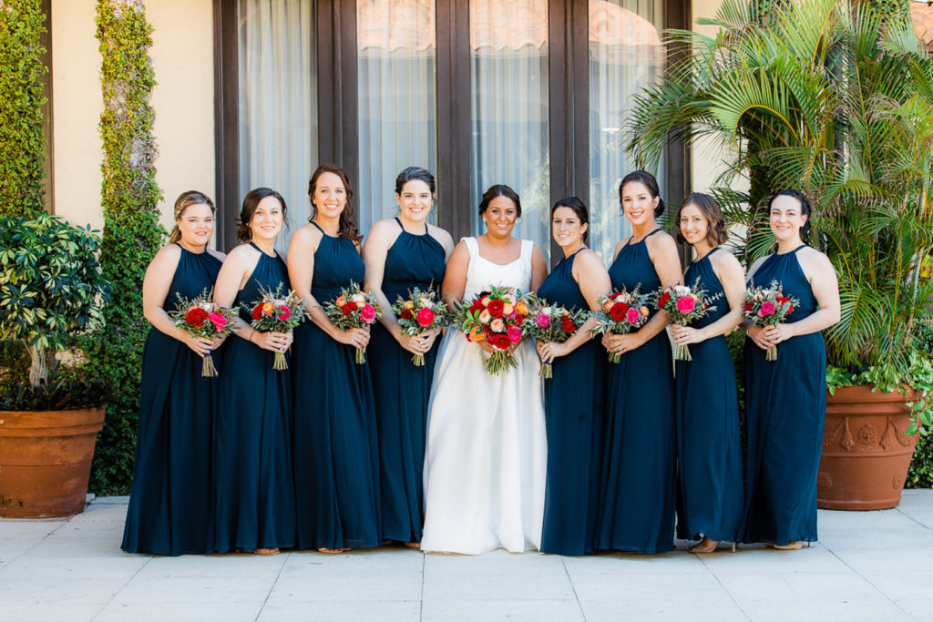 Bride and Bridesmaids in Matching Halter Navy Blue Dresses Holding Jewel Tone Floral Bouquets