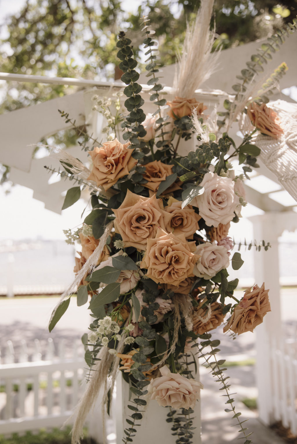 Neutral Cream and Burnt Orange Rose Detail on Wedding Alter with Mixed Greenery and Pampas Leaves   Boho Florida Waterfront Wedding Ceremony