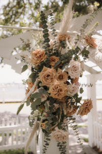 Neutral Cream and Burnt Orange Rose Detail on Wedding Alter with Mixed Greenery and Pampas Leaves | Boho Florida Waterfront Wedding Ceremony