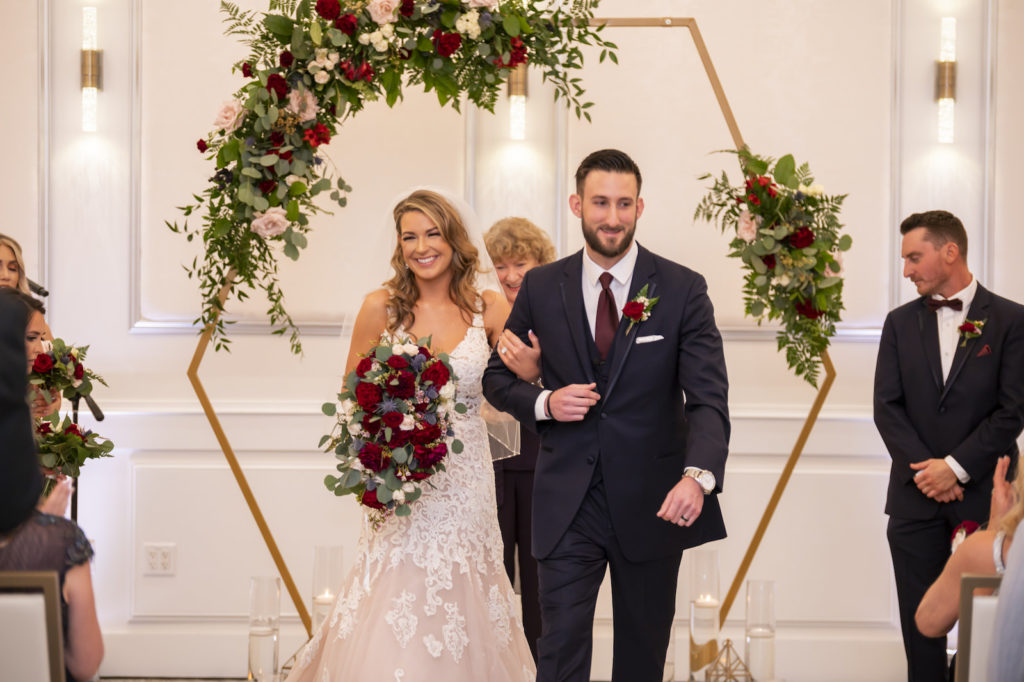 Florida Bride and Groom Exiting Wedding Ceremony First Kiss Under Gold Geometric Hexagonal Arch with Greenery and Blush Pink, Burgundy Roses   Tampa Bay Wedding Planner Coastal Coordinating