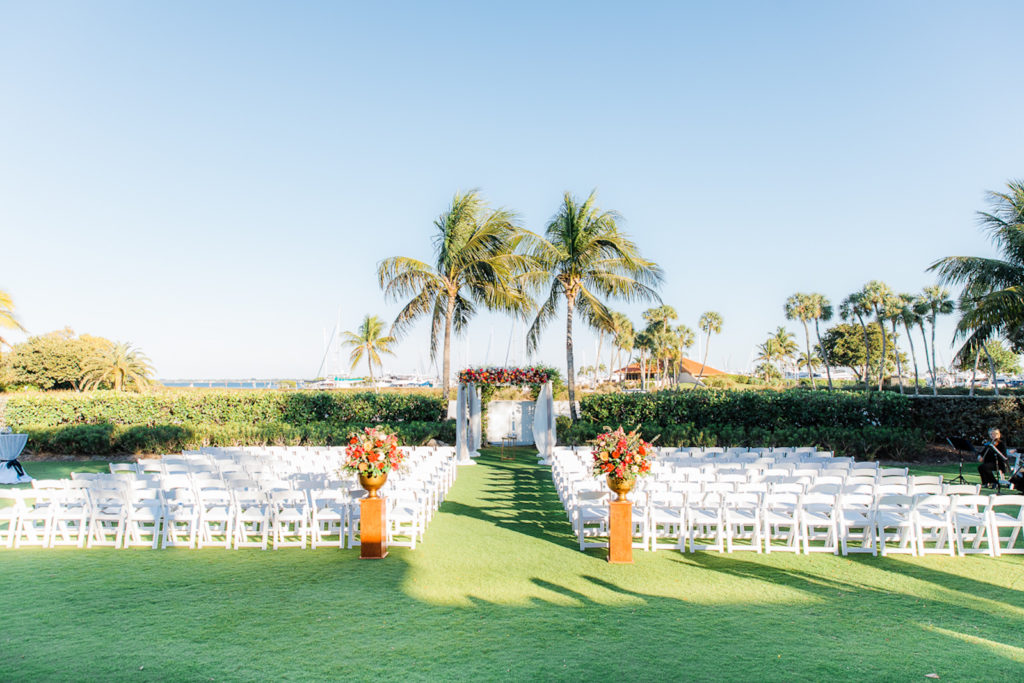Elegant Waterfront Outdoor Garden Wedding Ceremony Decor, White Folding Chairs, Tall Wooden Aisle Pedestals with Jewel Tone Floral Arrangements, Arch with White Linens and Flowers | Tampa Bay Wedding Venue The Resort at Longboat Key Club