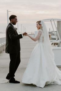 Timeless Elegant Groom Looking at Bride in Full Skirt Wedding Dress Crystal Rhinestone Embellished Illusion Long Sleeve Bodice and Full Length Veil on Dock of Tampa Bay Wedding Venue Westshore Yacht Club