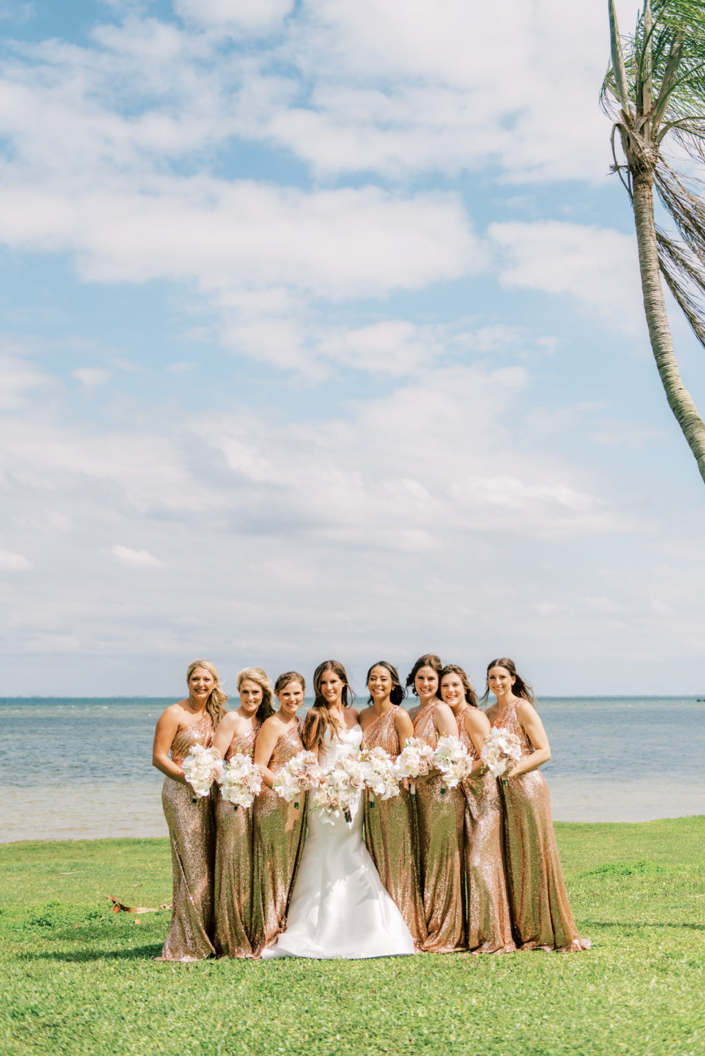 Florida Bride and Bridesmaids in Matching One Shoulder Rose Gold Sequin Dresses Waterfront Outdoor Photo | Tampa Bay Wedding Photographer Kera Photography