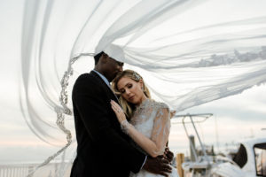 Creative Wedding Photo of Groom Holding Bride with Wedding Veil Blowing in Wind