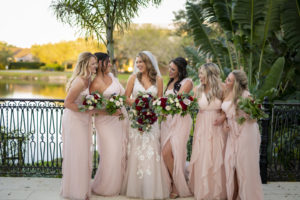 Florida Bride Holding Burgundy Roses and Greenery Floral Bouquet with Bridesmaids in Blush Pink Mix and Match Bridesmaids Dresses
