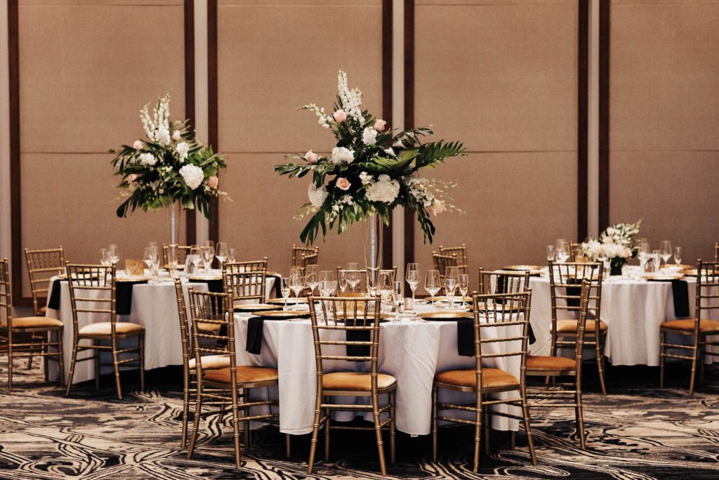 Gold Chiavari Wedding Chairs and White Linen Tables with Tall Tropical Floral and Greenery Centerpieces | Tampa Bay Rental Company Kate Ryan Event Rentals
