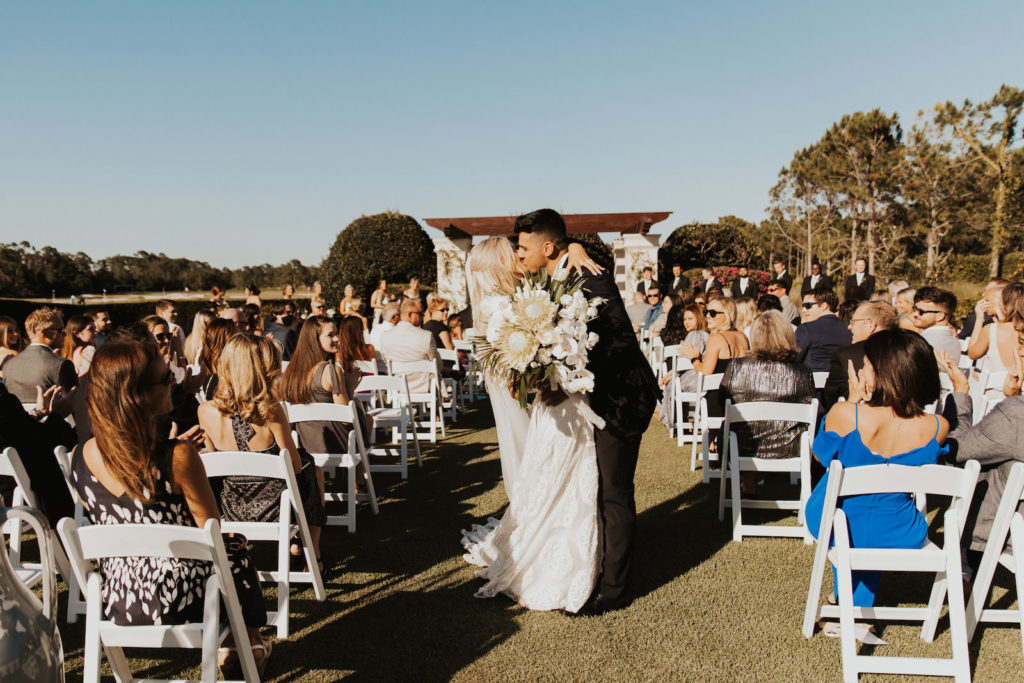 Timeless Bride and Groom Exiting Wedding Ceremony with Kiss in Aisle, Bride Holding Neutral Lush Floral Arrangement, King Proteas, Ivory Roses, Palm Fronds and Monstera Palm Leaves   Bradenton Wedding Venue The Concessions Golf Course