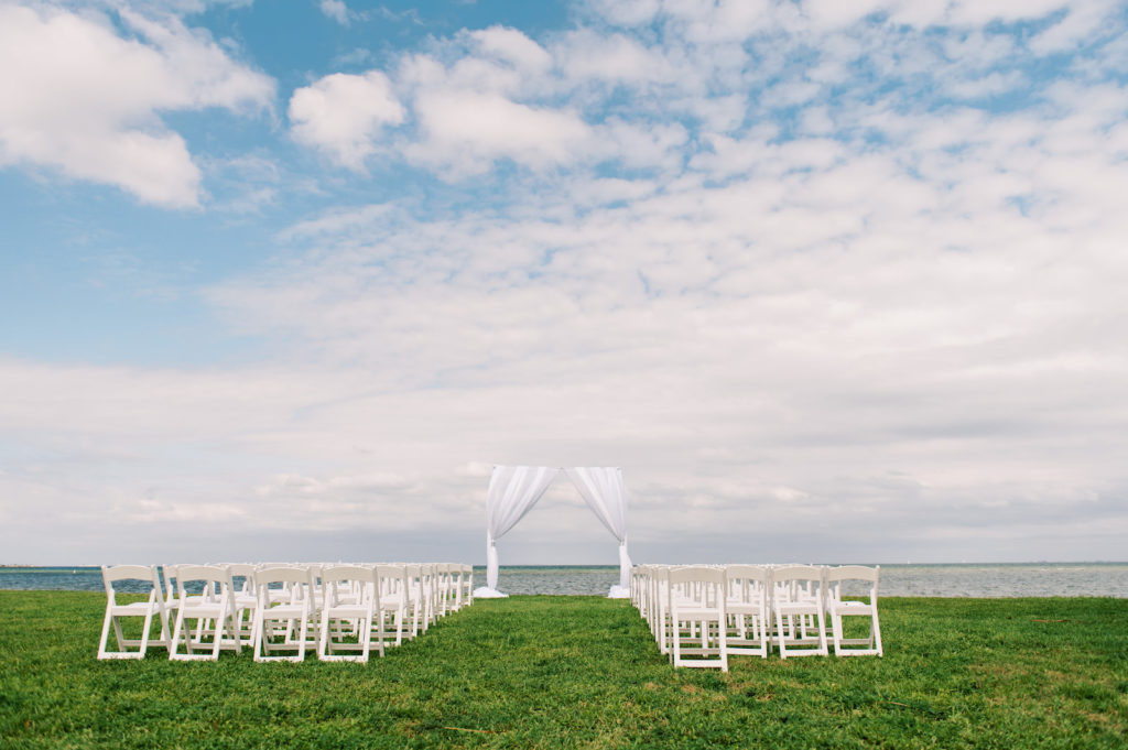 Waterfront Simple Classic Outdoor Wedding Ceremony Decor, Arch with White Linen Draping, White Folding Chairs | Tampa Bay Wedding Photographer Kera Photography | Wedding Venue Lassing Park